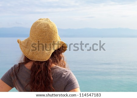 Woman with hat by the sea