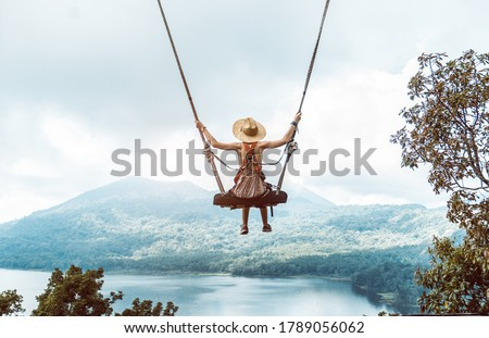 Woman with hat enjoying freedom on a swing in Bali, Indonesia. Life, adventure and peaceful feelings Stock foto ©