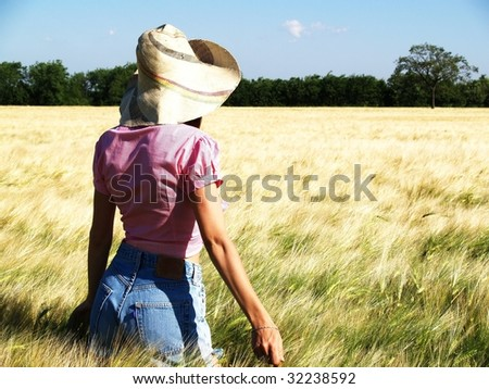 woman with hat in a wheat field