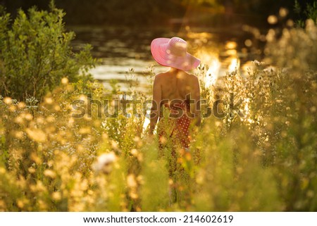 Woman with hat on the waterfront of meadow flowers #214602619