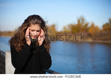 woman with headache in park