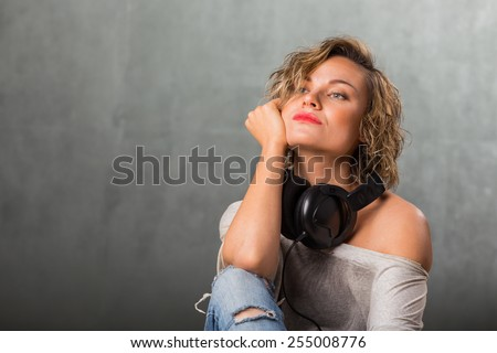 Woman with headphones. Blonde listening to music on stereo headphones. Emotions while listening to music.