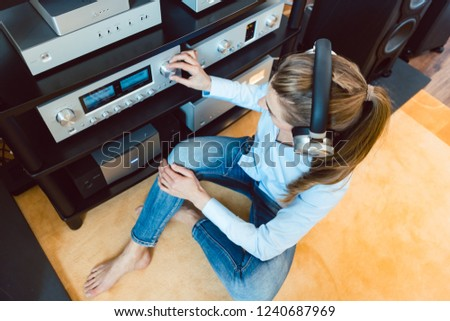 Woman with headphones listening to music via the Hi-Fi stereo in her home