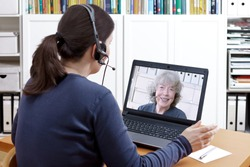 Woman with headset at her desk in front of her laptop having a video chat with her happy grandmother, text space