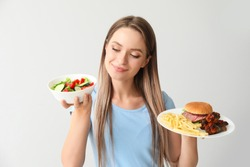 Woman with healthy and unhealthy food on light background. Diet concept