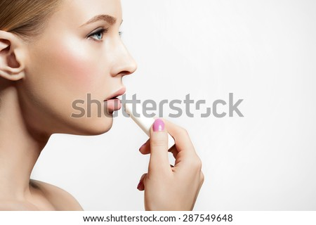 Woman with healthy skin applying a protective lip balm n a white background