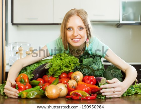 woman with heap of vegetables in kitchen