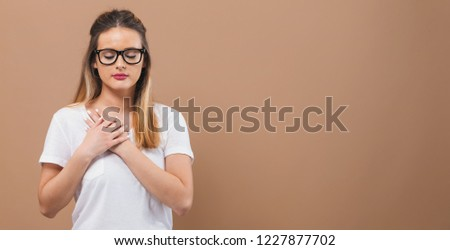 Woman with heartfelt expression on a brown background