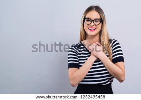 Woman with heartfelt expression on a gray background