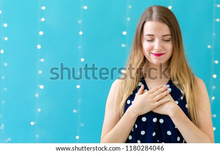 Woman with heartfelt expression on a shiny light background