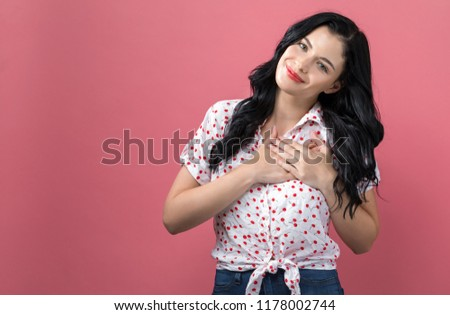 Woman with heartfelt expression on a solid background