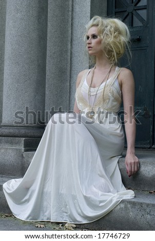 Woman with heavy makeup sitting on a step with a long white dress on