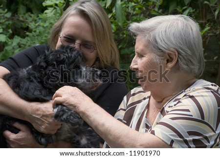 Woman with her elderly mother and a puppy relaxing in a garden