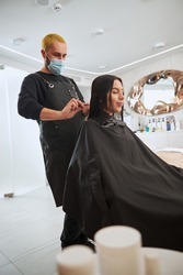 Woman with her eyes shut having her tresses combed by a focused coiffeur in a face mask