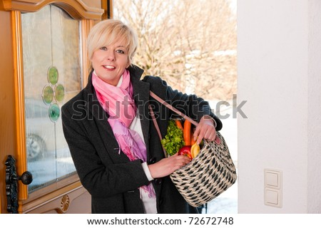 Woman with her groceries entering her home