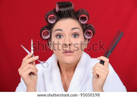 Woman with her hair in curlers holding scissors and a comb - stock photo