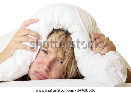 Woman with her head under her pillow trying to sleep