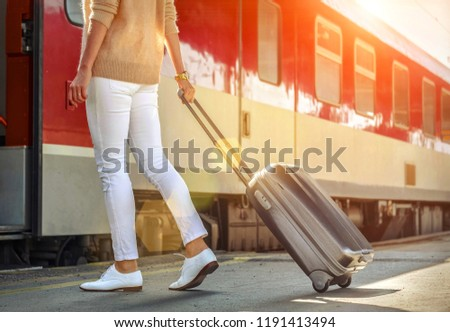 Woman with her luggage go  to red train on the peron of rail station under sun light at sunny day. #1191413494