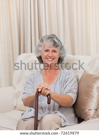 Woman with her walking stick at home - stock photo