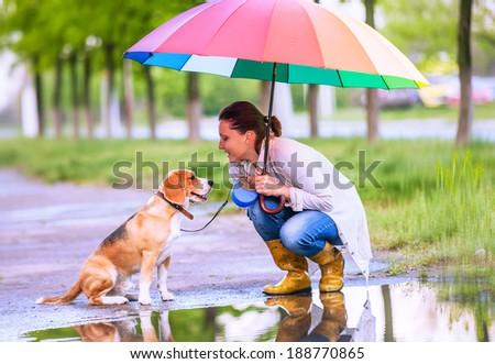 Woman with his beagle dog sitting under big bright umbrella