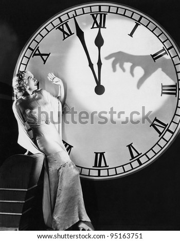 Woman with huge clock recoiling from frightening hand