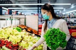 Woman with hygienic mask buying in supermarket grocery store for fresh greens,budget shopping during the pandemic.Natural source of vitamins and minerals.Covid-19 quarantine preparation