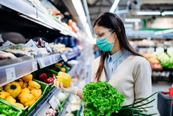 Woman with hygienic mask buying in supermarket grocery store for fresh greens,shopping during the pandemic.Natural source of vitamins and minerals.Plant based diet.Covid-19 quarantine preparation