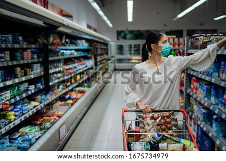 Woman with hygienic mask shopping for supply.Budget buying at a supply store.Emergency to buy list.Shopping for enough food and cleaning products.Preparation for a pandemic quarantine due to covid-19