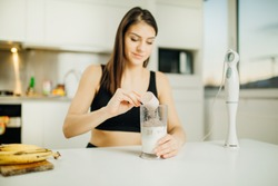 Woman with immersion blender making banana chocolate protein powder milkshake smoothie.Adding a scoop of low carb whey protein mix to shake after a home workout.Diet after the gym.Healthy lifestyle
