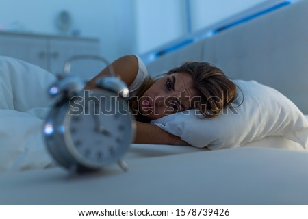 Woman with insomnia lying in bed with open eyes. Girl in bed suffering insomnia and sleep disorder thinking about his problem at night
