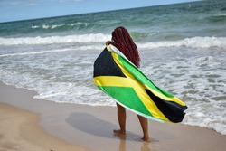 Woman with Jamaican flag walking along beach