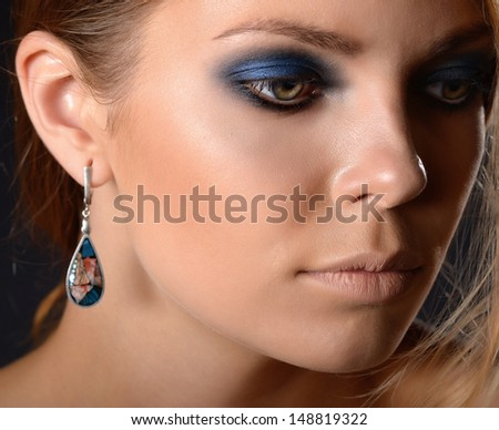 Woman with jewelry. Portrait on dark background.