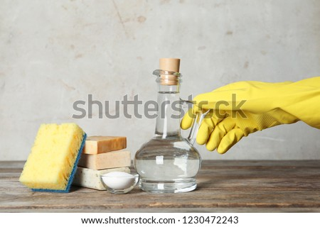 Woman with jug of vinegar and cleaning supplies at table Foto stock ©