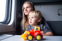 Woman with kid in a train compartment looks out the window. Family travel, holidays.