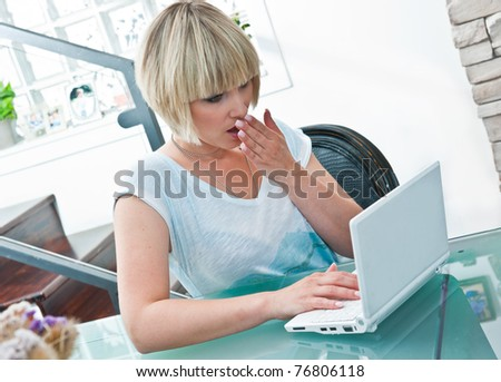 woman with laptop computer sitting at the table in living room