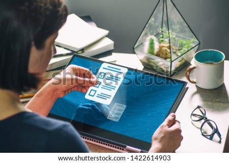 Woman with laptop on her desk. She holds a questionnaire icon. Concept of online testing, questionnaires, voting. Image