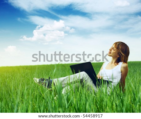 Woman with laptop sitting on green grass
