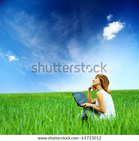 Woman with laptop sitting on green meadow and looking to a sky