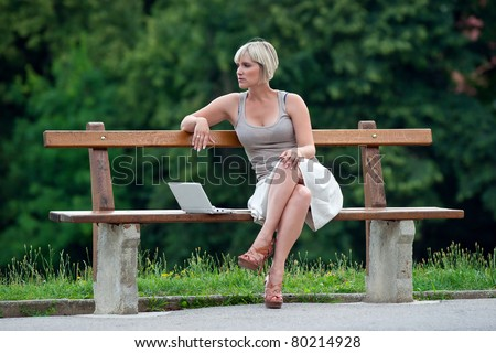 woman with laptop sitting on the bench in the park - stock photo