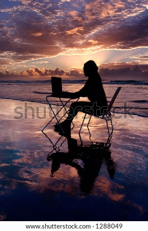 Woman with laptop working at sunrise