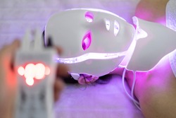Woman With Led Light Therapy Facial Beauty Mask Photon Therapy. Woman receiving face light therapy in LED mask.