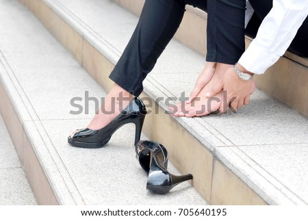 Woman with leg cramps and ankles from high heels. She sat on the stairs holding her leg. #705640195