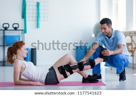 Woman with leg injury on mat and smiling doctor during treatment in the hospital