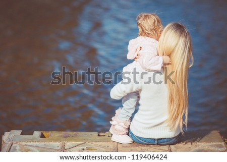 Woman with little daughter sitting near water turned back