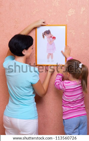 Woman with little girl hang up a picture (portrait of same girl)