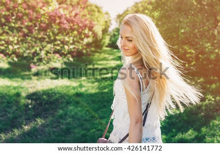 Stock Photo Woman with  long blond hair in the garden with flowers. Beautiful girl on a sunny day.