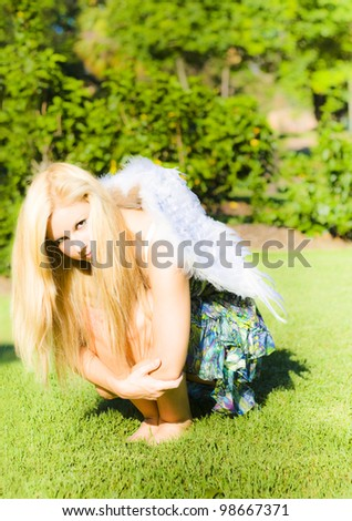 Woman with long blonde hair squatting arms around her knees, with feather wings on her back in a broken wings concept