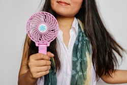 Woman with long brunette hair, wears white shirt with scarf, holding portable pink fan in white background