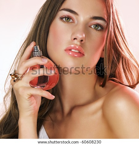 Woman with long hair applying perfume on her hair