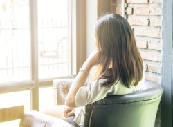 Woman with long hair sitting back and looking outside the window,a happy holiday.